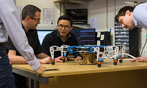Researchers in discussion around a robotic spider