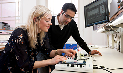 Two researchers demonstrating how to use intricate electrical equipment