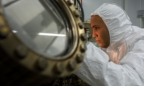 A male researcher operating a molecular beam epitaxy