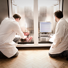 Two researchers in lab coats knelt on the floor, adjusting PC wires