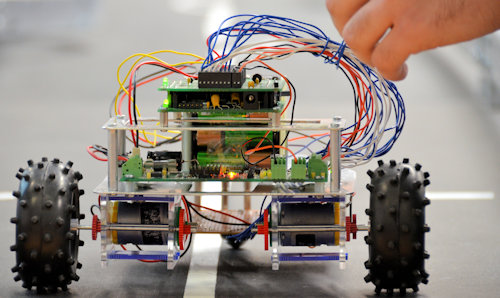 A small robotic car, with inner workings exposed