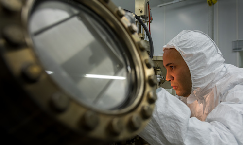 Man in full protective suit peering into a piece of equipment