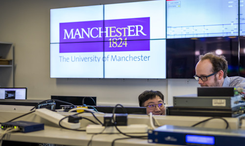 Two men looking at electronic equipment on a table, while a large screen behind contains The University of Manchester logo