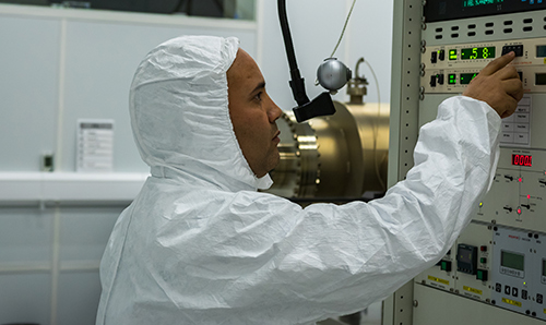 A researcher operating equipment in the molecular beam epitaxy laboratory