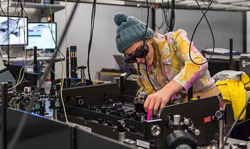 Researcher crouched over equipment in the PSI