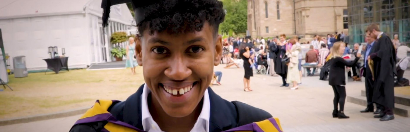 A student smiles at the camera, wearing a black graduation cap and gown.