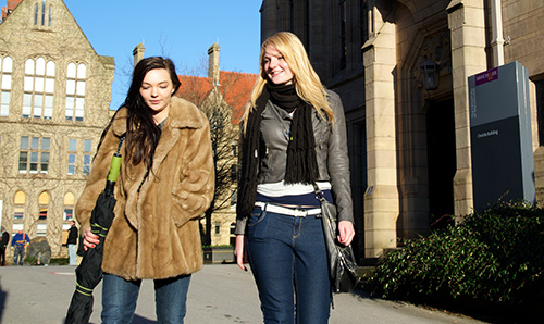 Two female students walking and talking on campus